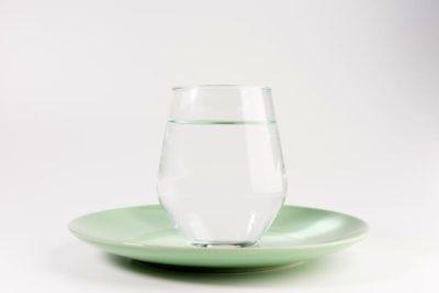 Vaso de agua en un plato vacío