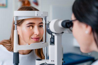 oftalmologo examina ojo rojo de una paciente